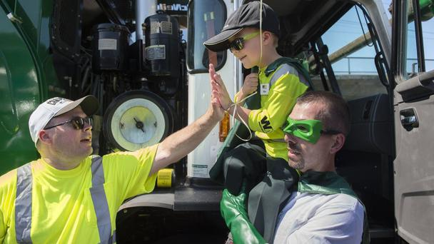 Ethan gets a high-five while carried by Captain Recycle, Mitch Zak, during one of his stops (Sacramento Bee/AP)