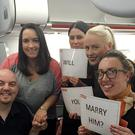 Matthew Hedges and finance Zosia Katnik with cabin crew after he popped the question in mid-air on the way to Majorca (easyJet)