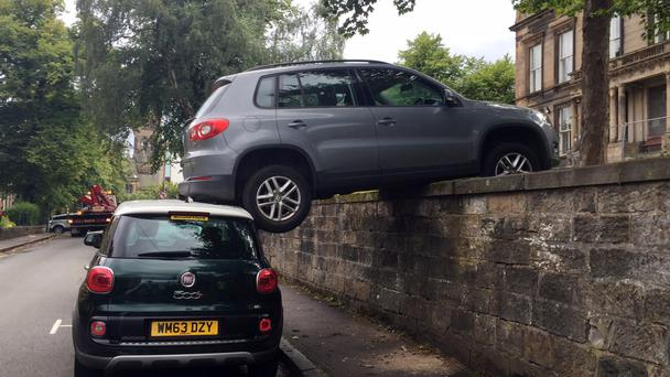 A Volkswagen on top of a Fiat 500 after the car rolled backwards down a hill and over a wall on Southpark Avenue in Glasgow's West End