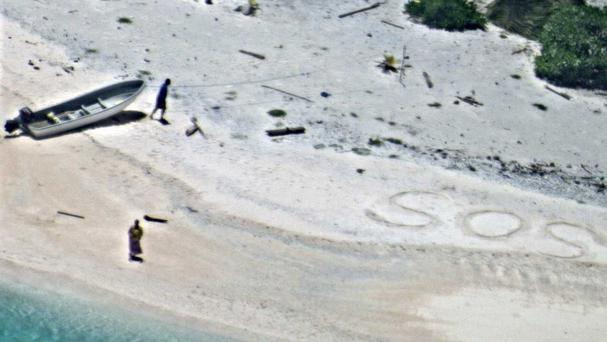 The pair were spotted on the beach alongside their SOS sign (US Navy via AP/PA Wire)