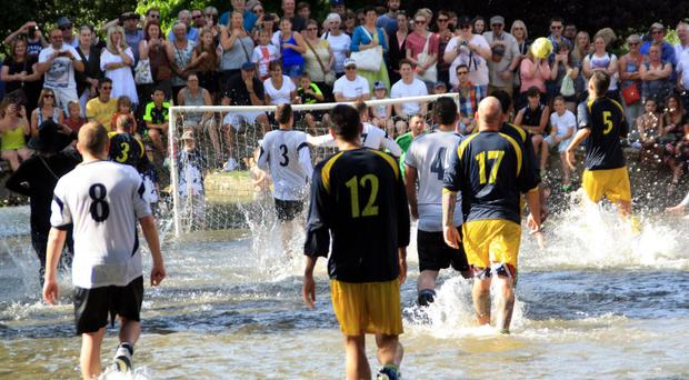 Members of Bourton Rovers 1st XI (dark blue shirts) and the club's 2nd XI battle for the ball during the annual Football In The River match in Bourton-on-the-Water, Gloucestershire