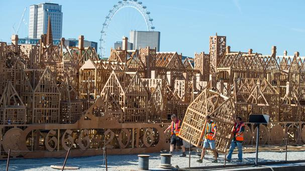 Workers apply the finishing touches to a 120-metre long model of London's skyline in the 17th century