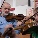 Labour leader Jeremy Corbyn is given a violin lesson by 10-year-old Jessica Kelly