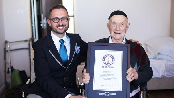 Israel Kristal, right, at the age of 112, when he was presented with his certificate of achievement for being the world's oldest living man