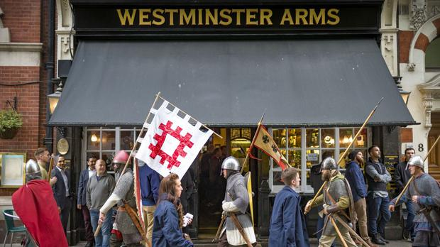 Battle of Hastings re-enactors pass a pub in London on their 300-mile march to Hastings from Clifford's Tower in York (English Heritage/PA)