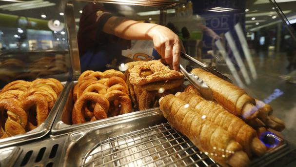 On a roll - an Auntie Anne's 'pretzel dog' about to go down the hatch at a Kuala Lumpur shopping mall (AP)
