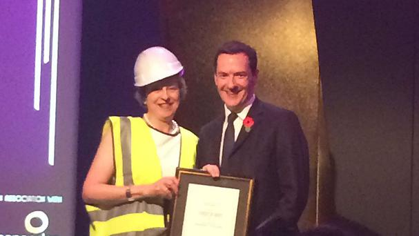 Prime Minister Theresa May who appeared to mock George Osborne by accepting an award from the former chancellor wearing a high-visibility jacket and hard hat (Robbie Gibb/Twitter/PA)