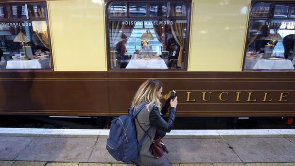 A commuter prepares to board the vintage Belmond British Pullman train at Ashford International station in Kent for a surprise luxury journey to London