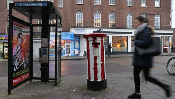 A post box on Bargate Street in Southampton, which has been painted with the white stripes of Southampton FC
