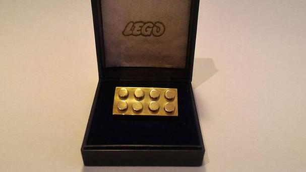 A solid gold Lego brick which is expected to sell for more than £12,000 under the hammer.