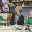 Theresa May pulls a face as she talks to Year Six pupils during a visit to Captain Shaw's Primary School in Bootle, Cumbria