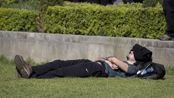 A man enjoys the sunshine at Parliament Square in central London, on what is expected to be the hottest day of the year so far.