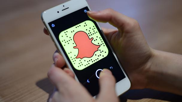 A general view of a woman holding a mobile phone with the Snapchat app.