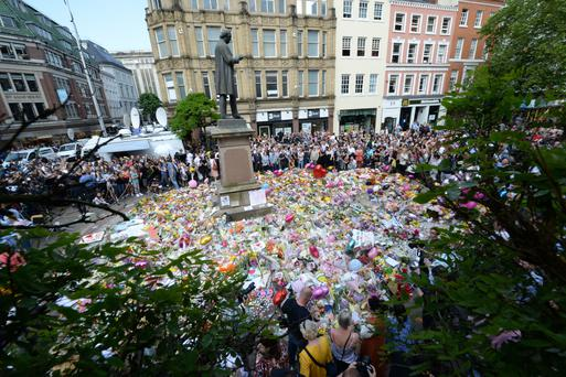 Crowds look at the floral tributes after a minute's silence in St Ann's Square, Manchester, to remember the victims of the terror attack. Picture: PA