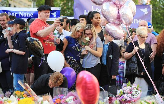 People gather to pay tribute tot hose who died in the Manchester bombing Photo: PA