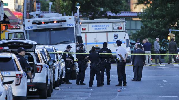 Emergency personnel stand near the scene where a police officer was fatally shot (Seth Wenig/AP/PA)