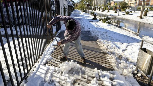 Marcelo Elias, 43, cleans snow and ice off the sidewalk in front of house in Santiago, Chile (Esteban Felix/AP)