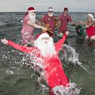 Santas enjoy a dip in the sea – in full costume (Tobias Nicolai/AP)