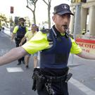 A policeman warns people from the street in Barcelona