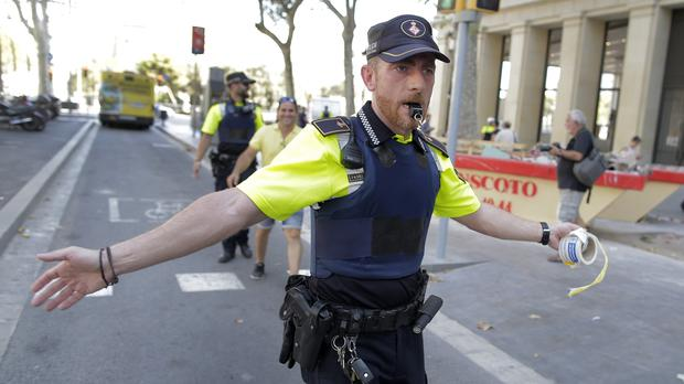 A policeman warns people from the street in Barcelona.