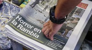 A man touches a newspaper displaying a photograph of the aftermath of the terror attack in Las Ramblas
