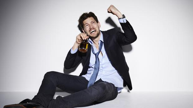 Angry man drinking and shaking fist