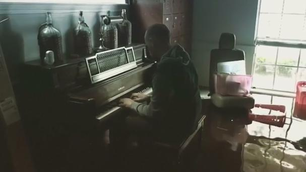 Aric Harding plays his piano in his flooded Friendswood home in Texas (Aric Harding/Instagram)