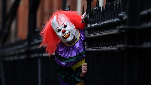 A person wearing a clown costume in a street in Liverpool