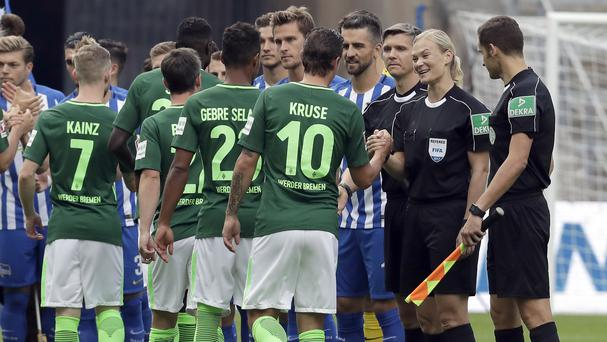 Referee Bibiana Steinhaus shakes the hands of footballers before a Bundesliga match