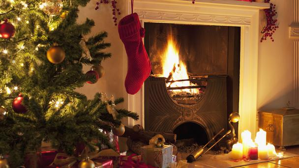 Christmas tree and stocking next to a lit fireplace (Tom Merton/Getty Images)