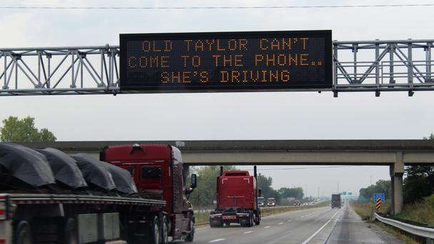Message board in Iowa reading Old Taylor can't come to the phone.. she's driving (Zero Fatalities/Iowa Department of Transport)
