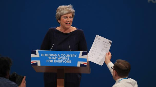 Theresa May is handed what looks like a P45 by a prankster (Peter Byrne/PA)