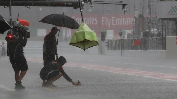 A team mechanic places a paper boat in the pit lane at a practice session for the Japanese Grand Prix