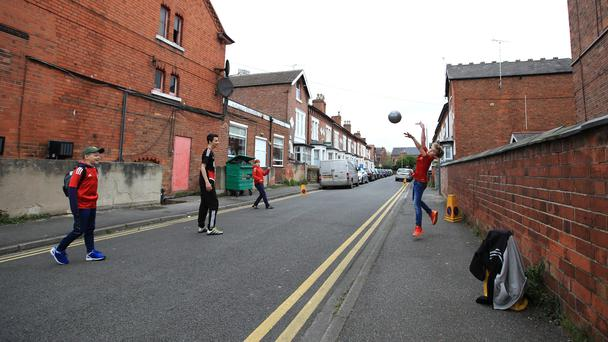 Children play football in the streets before a Championship football match