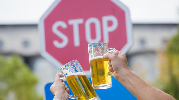 Glasses clink in front of a stop sign(zoff-photo/Getty/PA)