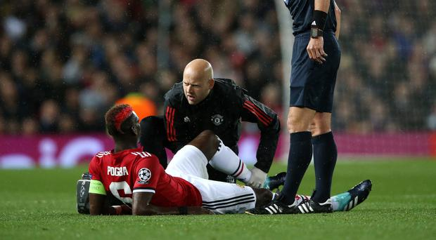 Manchester United midfielder Paul Pogba lies injured on the ground