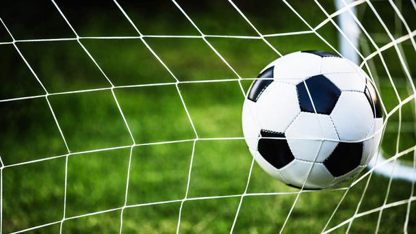 A football hits the back of the net