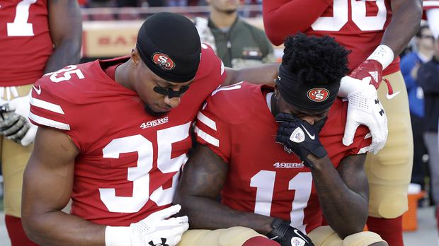 San Francisco 49ers safety Eric Reid (35) and wide receiver Marquise Goodwin (11) kneel during the performance of the national anthem before an NFL football game