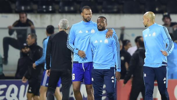 Marseille's Patrice Evra, center right, is led away by his teammate after an incident with Marseille supporters that saw him sacked