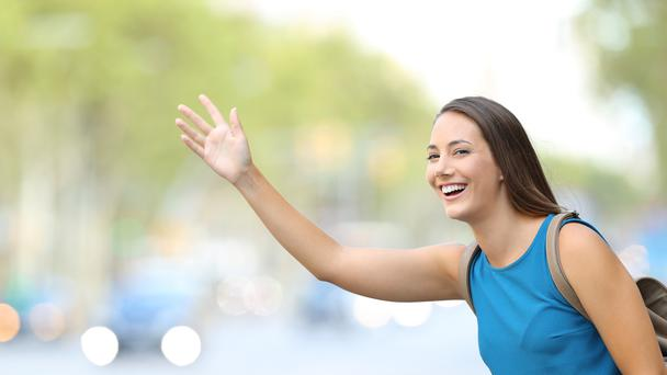 A woman waving on the street
