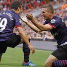 Lukas Podolski celebrates scoring a goal against Liverpool for Arsenal