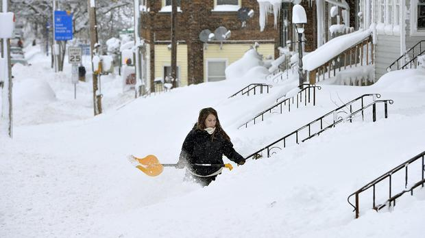 Someone shovels snow after record snowfall in Erie, Pennsylvania
