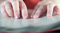 Person reading Braille (portokalis/Getty Images)
