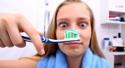 A girl looking at a toothbrush