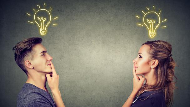Two people with light bulbs above their heads