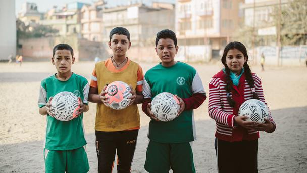Children hold footballs donated by Park Social Soccer Co (Kim Landy/Park)