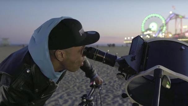 Someone takes a look at the moon through a telescope