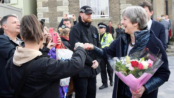 Prime Minister Theresa May fist bumps a member of the public (Toby Melville/PA)