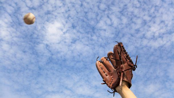 A hand in a baseball glove ready to catch the ball