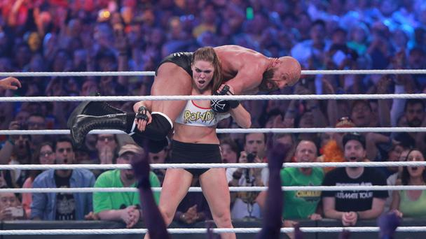 Rousey with Triple H on her back
